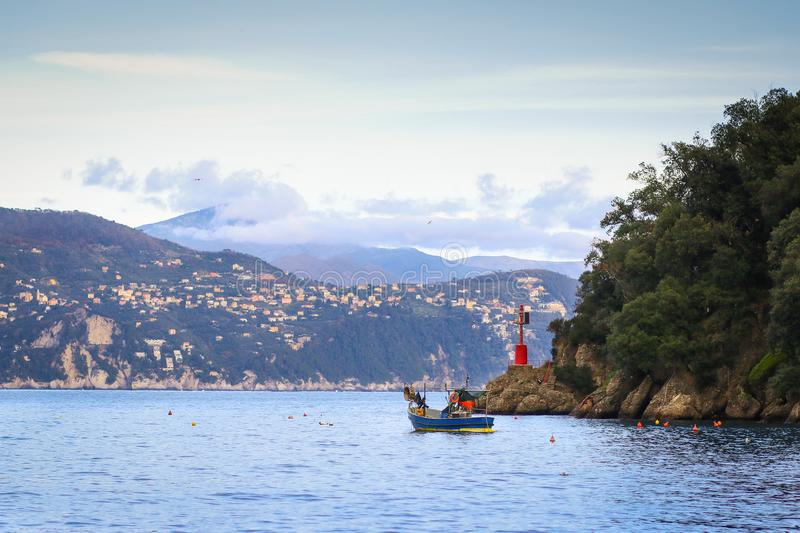 Small fishing boat at the entrance in the bay at Portofino stock images