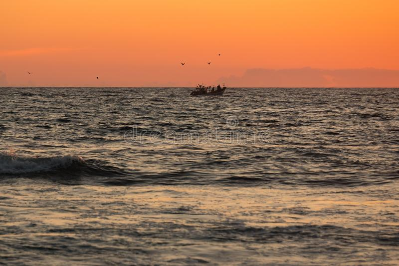 Small fishing boat on the ocean at sunset royalty free stock photography