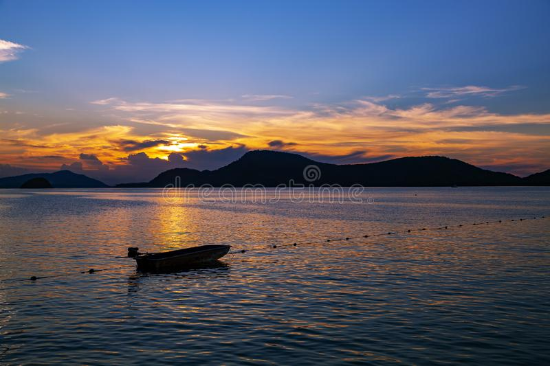 Small fishing boat in the sea sunset scenery, Beautiful Landscape and light of nature in evening with beautiful colors Clouds and. Sky royalty free stock image