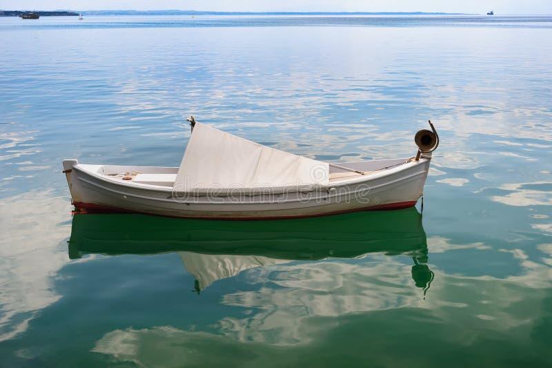 Small fishing boat at sea surface royalty free stock image