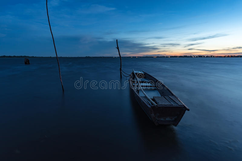 Small fishing Boat in twilight. Small fishing boat is parking on bay in sunset after fishingman work all day. It is life style of almast people in water resource royalty free stock photography