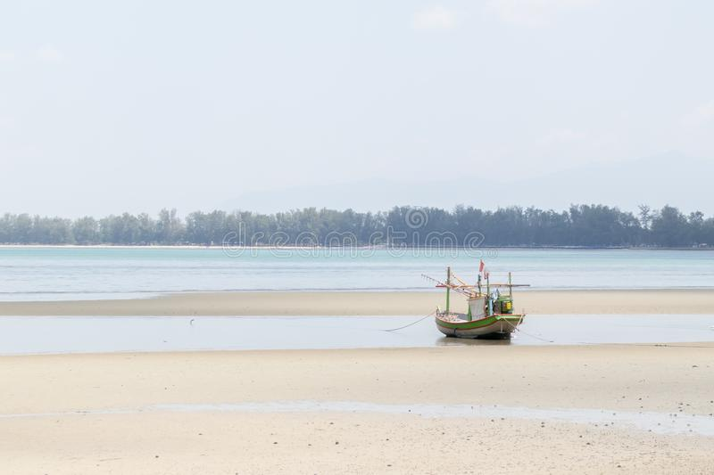 Small fishing boats aground on the beach with trees in the background. Small fishing boats aground on the beach with trees in the background stock images