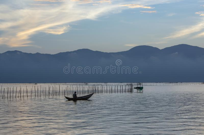 Small fishing boats and lonely man in the bay with magic of the sky and clouds at sunrise part 3 stock photo