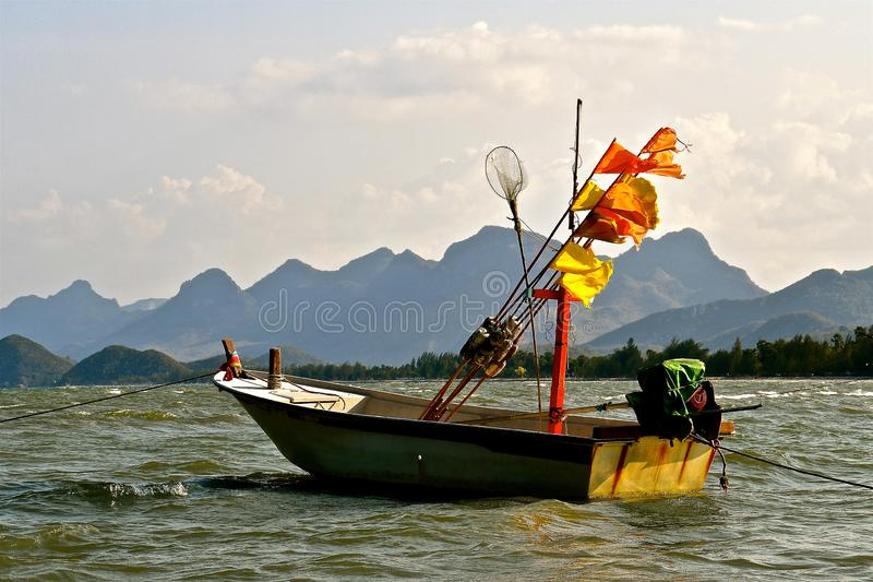 Small Fishing dinghy. In choppy waters, against a backdrop of forest and rugged hills stock photo