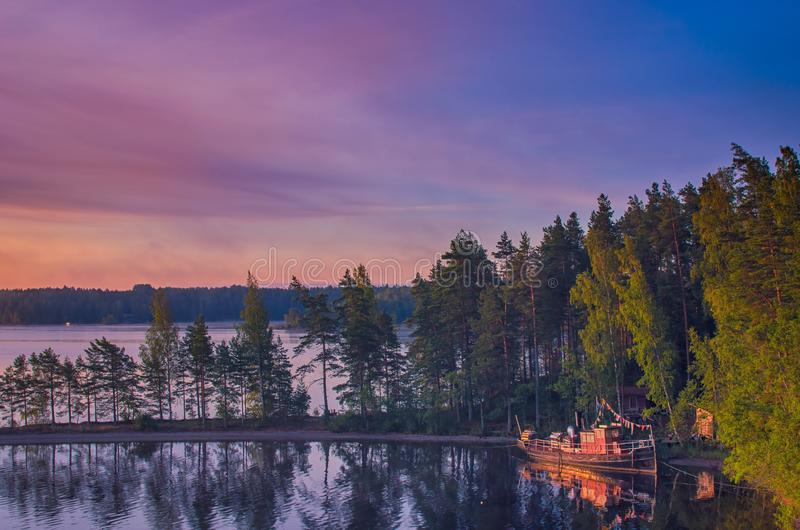 Small fishing or pleasure boat boat moored on Paijanne lake. Beautiful sunrise scape with stone beach, pine forest and water. Lake royalty free stock images