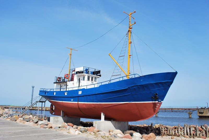 Small fishing ship. Monument on the sea coast royalty free stock photo