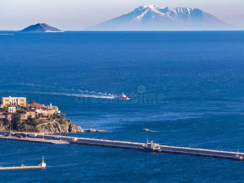 Small fishing ship coming to a port, big island mountain in the background royalty free stock photos