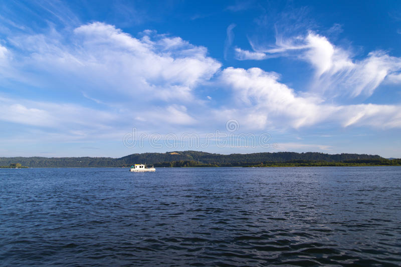 Small fishman boat on Columbia river on delightful panorama of w. Panorama of the Columbia River to the mountain range on the horizon, a small fishing boat with stock image