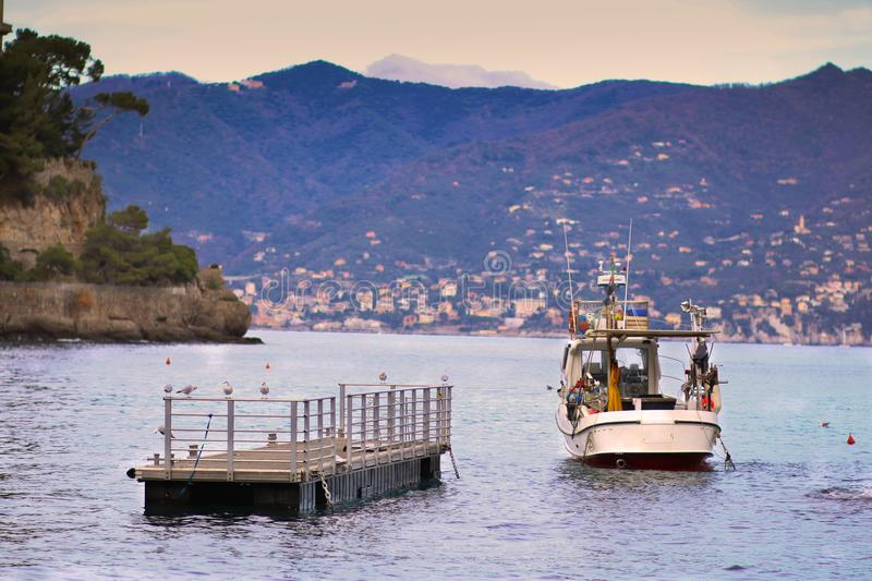 Small floating dock and a small fishing boat at the entrance in the bay at Portofino stock photos