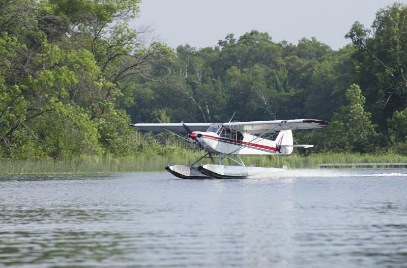 Small floatplane lands on a Minnesota lake stock photos