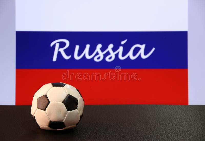 Small football on the black floor and Russian nation flag with the text of Russia background. The concept of sport stock photos