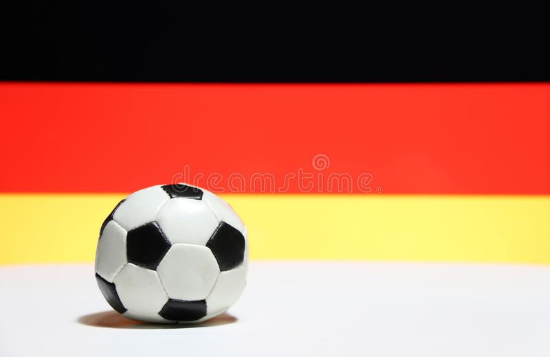 Small football on the white floor with black red and yellow color of German nation flag background. The concept of sport royalty free stock photo