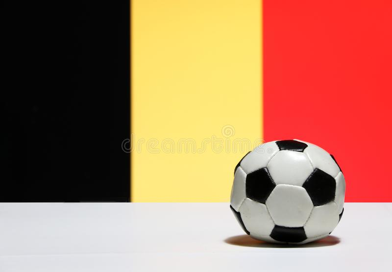 Small football on the white floor with black yellow and red color of Belgian nation flag background. The concept of sport royalty free stock images