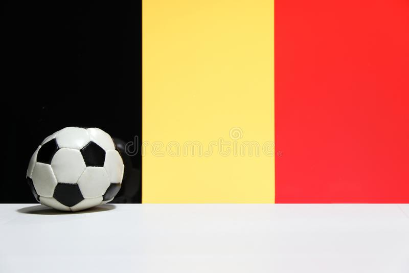 Small football on the white floor with black yellow and red color of Belgian nation flag background. The concept of sport stock photos
