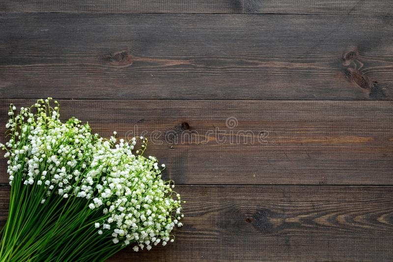 Small and fragrant spring flowers. Bouqet of lily of the valley flowers on dark wooden background top view copy space. Small and fragrant spring flowers. Bouqet stock photo
