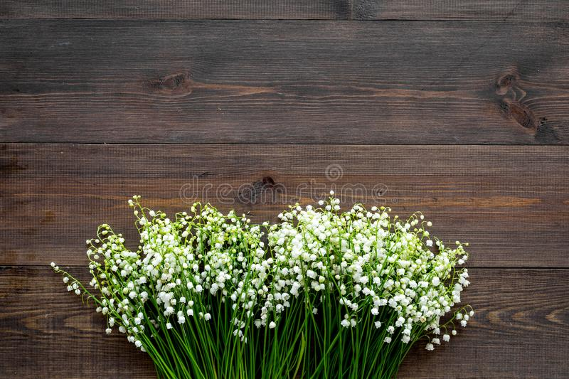 Small and fragrant spring flowers. Bouqet of lily of the valley flowers on dark wooden background top view copy space. Small and fragrant spring flowers. Bouqet royalty free stock images