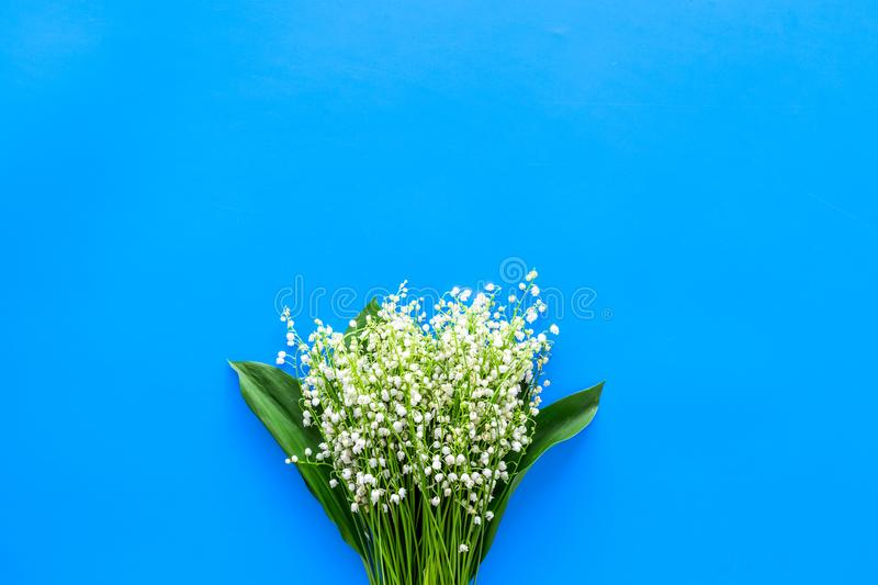 Small and fragrant spring flowers. Bouqet of lily of the valley flowers on pastel blue background top view copy space. Small and fragrant spring flowers. Bouqet stock photos