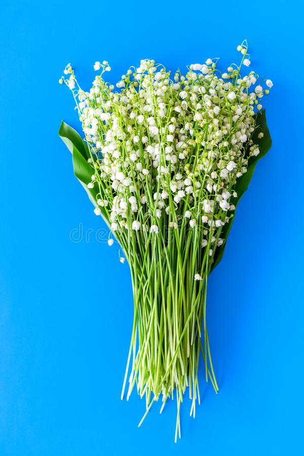 Small and fragrant spring flowers. Bouqet of lily of the valley flowers on pastel blue background top view.  stock photo