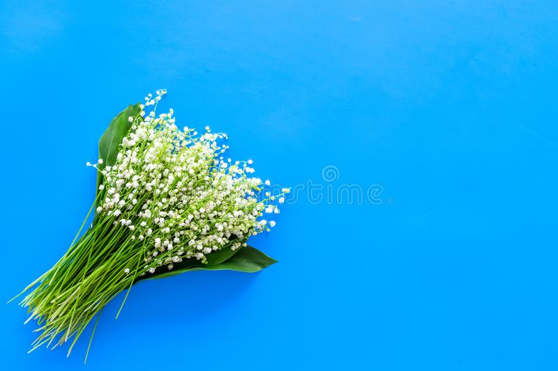Small and fragrant spring flowers. Bouqet of lily of the valley flowers on pastel blue background top view copy space. Small and fragrant spring flowers. Bouqet stock photo