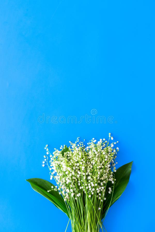 Small and fragrant spring flowers. Bouqet of lily of the valley flowers on pastel blue background top view copy space. Small and fragrant spring flowers. Bouqet stock image