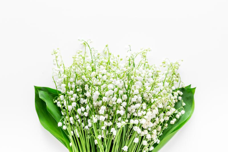 Small and fragrant spring flowers. Bouqet of lily of the valley flowers on white background top view copy space. May flowers. Bouqet of lily of the valley royalty free stock photography