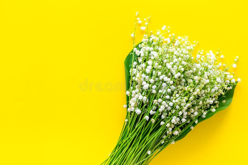 Small and fragrant spring flowers. Bouqet of lily of the valley flowers on yellow background top view copy space. Small and fragrant spring flowers. Bouqet of stock image