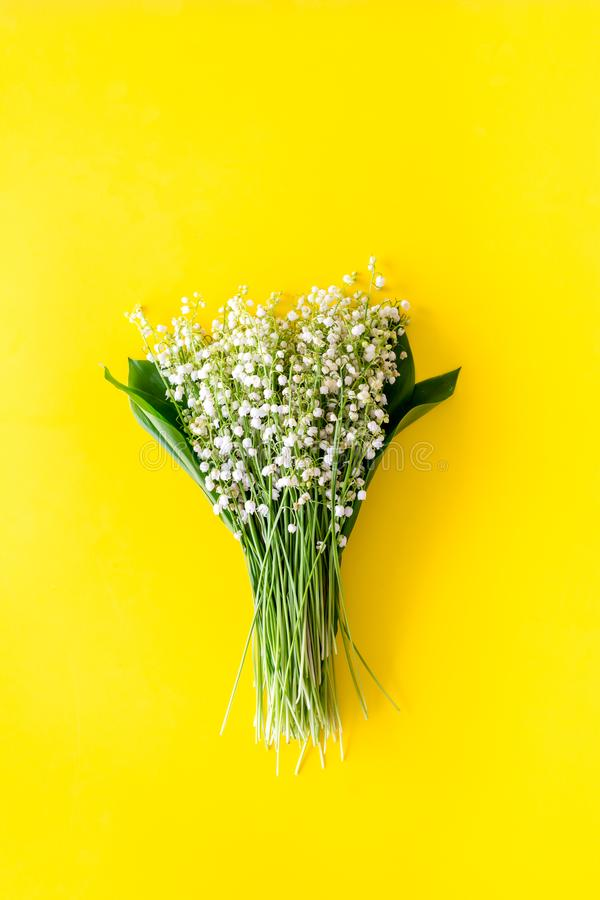 Small and fragrant spring flowers. Bouqet of lily of the valley flowers on yellow background top view copy space. Small and fragrant spring flowers. Bouqet of royalty free stock images