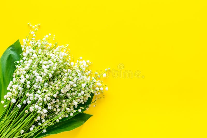 Small and fragrant spring flowers. Bouqet of lily of the valley flowers on yellow background top view copy space. Small and fragrant spring flowers. Bouqet of royalty free stock photography
