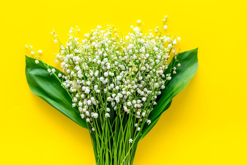 Small and fragrant spring flowers. Bouqet of lily of the valley flowers on yellow background top view copy space. Small and fragrant spring flowers. Bouqet of stock photo