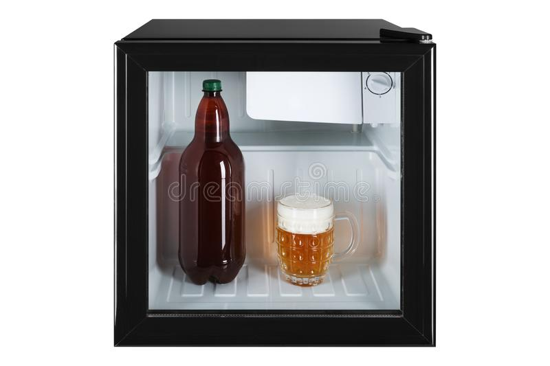 Small fridge bar, inside the bottle and glass full of beer with foam, the concept of summer and cooling royalty free stock photos