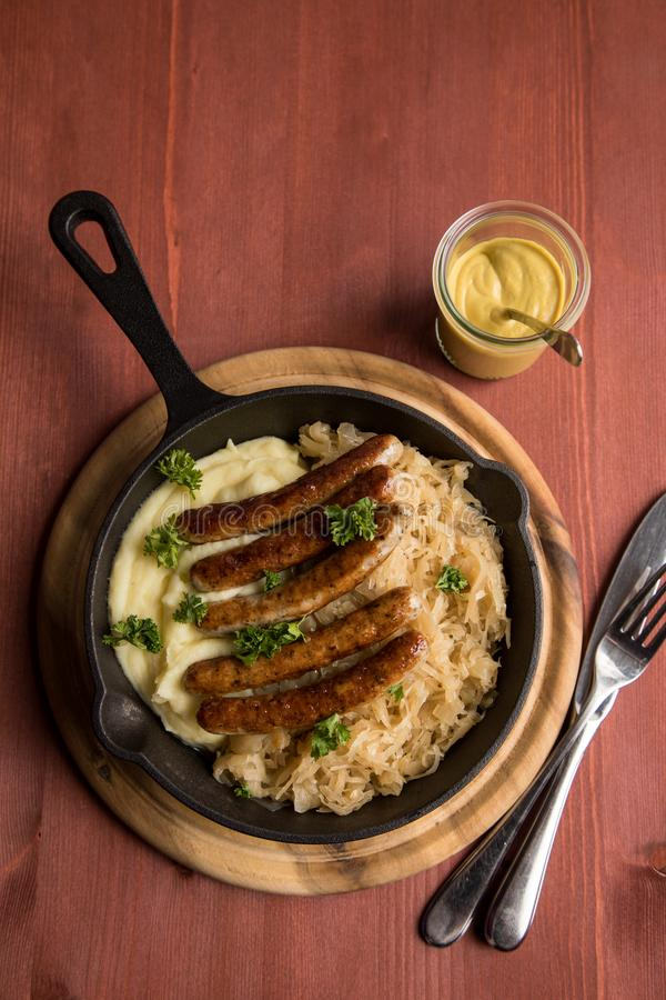 Small fried Bavarian German Nürnberger sausages with sauerkraut, mashed potatoes and mustard in iron cast pan on wooden board stock image