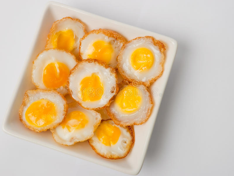 Small fried eggs on white dish. Francolin fried eggs on the white dish stock photos