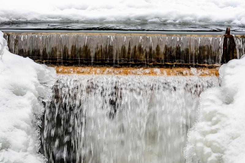 A small frozen waterfall, cold water, snow and ice, winter and frost stock image