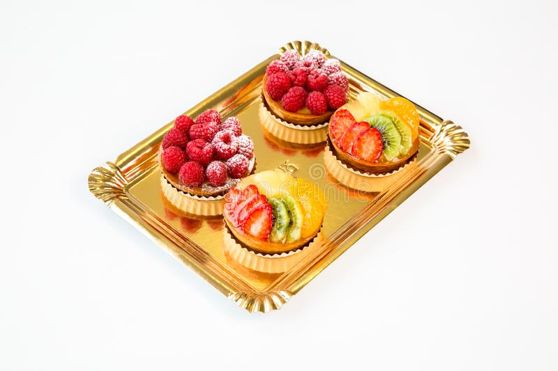 Small fruits cakes on a white background. Small raspberry and kiwi fruits cakes on a white background stock image