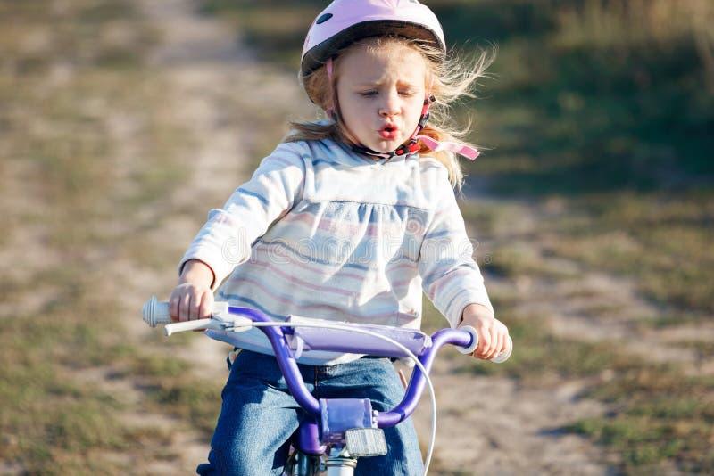 Small funny kid riding bike stock photo