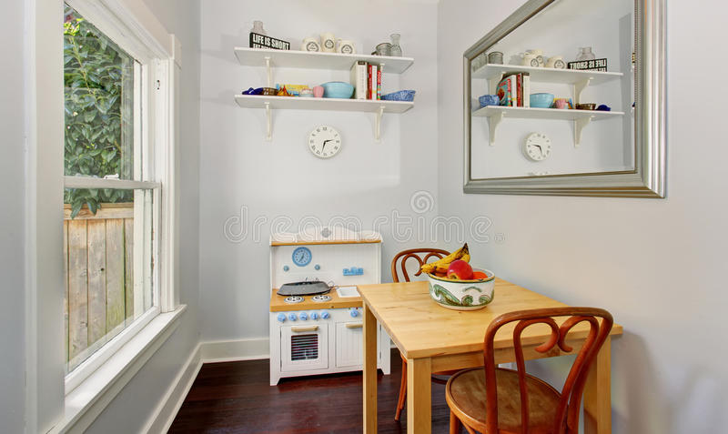 Small furniture in cozy kids playroom with white walls and one window. royalty free stock photo