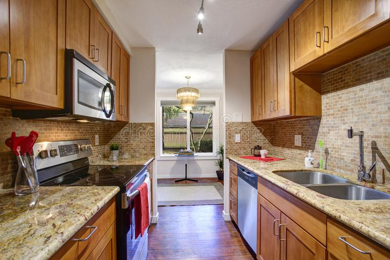 Small galley kitchen design with black kitchen appliances. Maple cabinets, granite countertops and backsplash stock photos