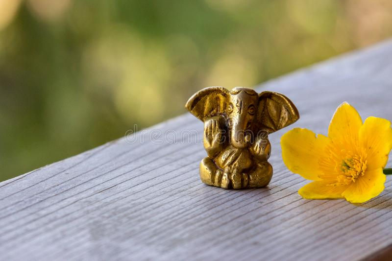 Small Ganesha figure with bright yellow flower. Beautiful Ganesh statue with open palm and blooming flower on wooden board. stock photos