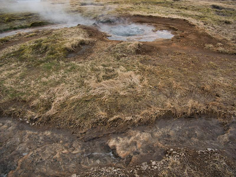 A small geothermal pool with boiling water royalty free stock photo
