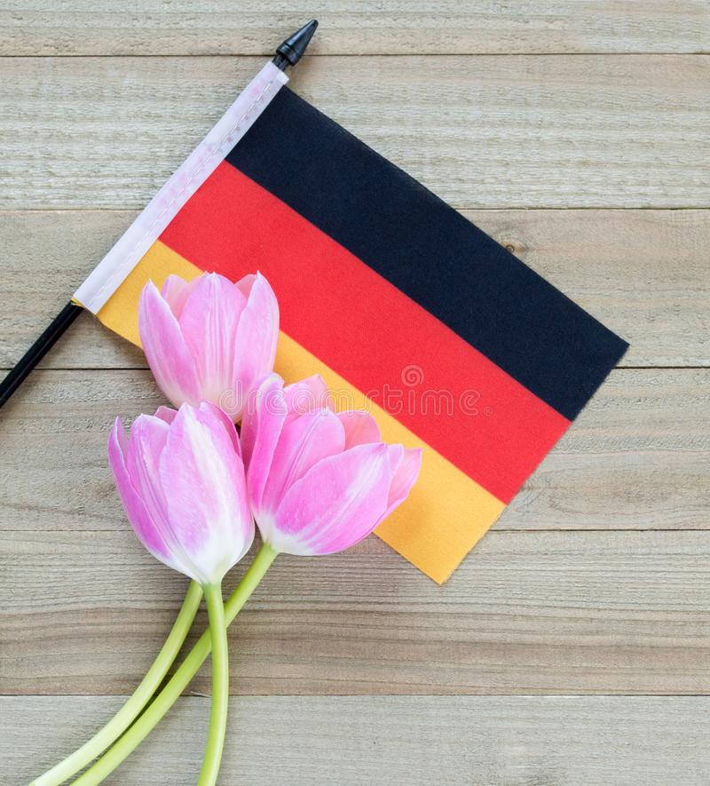 Small German flag with pink tulips on a wood background royalty free stock photos