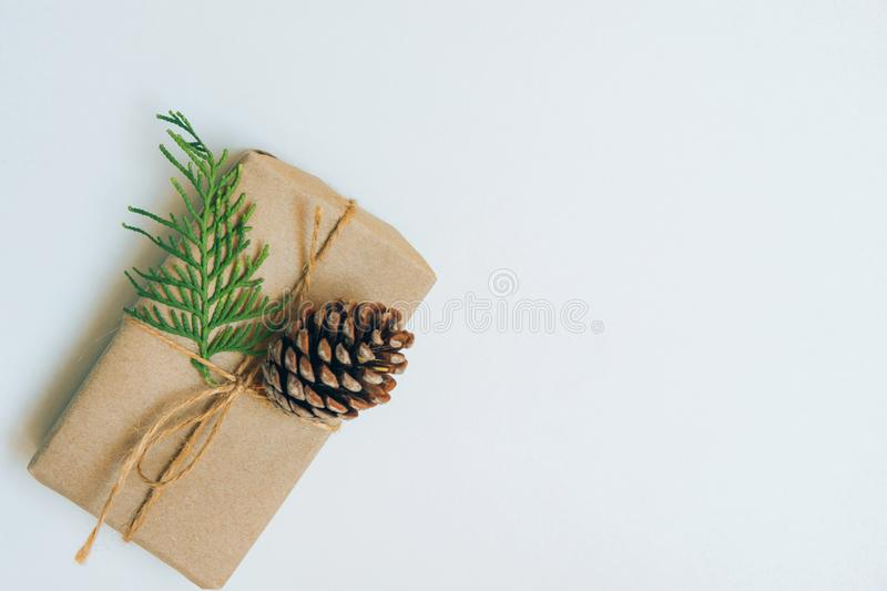 Small Gift Box Wrapped in Craft Paper with Juniper Twig and Pine Cone on White Background. Christmas New Years Presents Shopping royalty free stock images