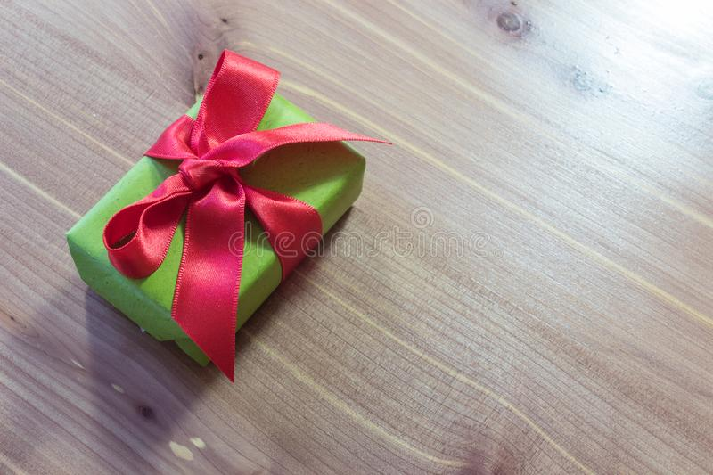 Small gift, diagonal on a wood table, wrapped in green with big red satin bow royalty free stock photos