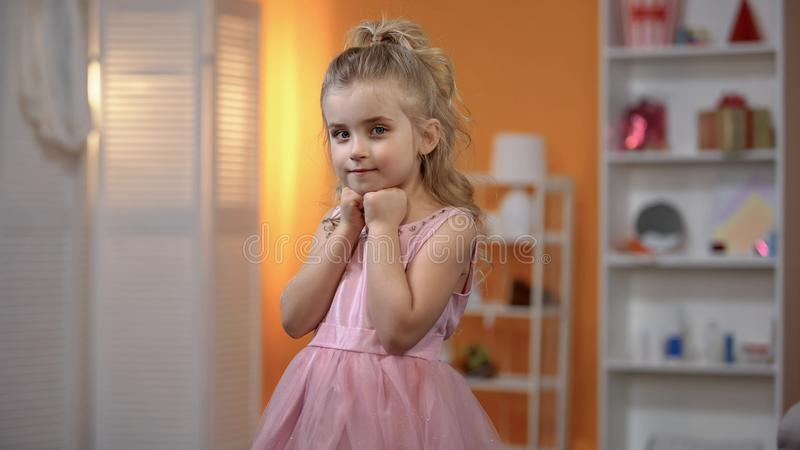 Small girl in beautiful dress posing for camera, making birthday photosession royalty free stock photo
