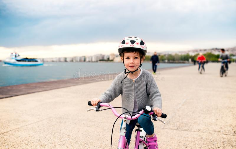 A small girl with bicycle cycling outdoors on beach. A small girl with helmet and bicycle cycling outdoors on beach stock images