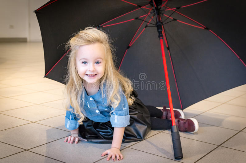 Small girl in car exhibition room. Small girl in exhibition room for car stock photography
