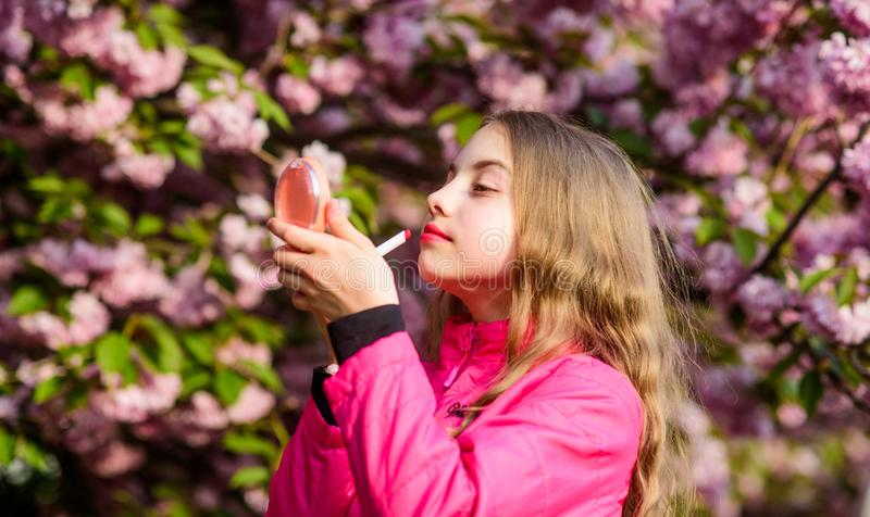 Small girl child in spring flower bloom. Smell of tender bloom. Sakura flower concept. Gorgeous flower and female beauty. Natural cosmetics for skin. Girl in stock photo
