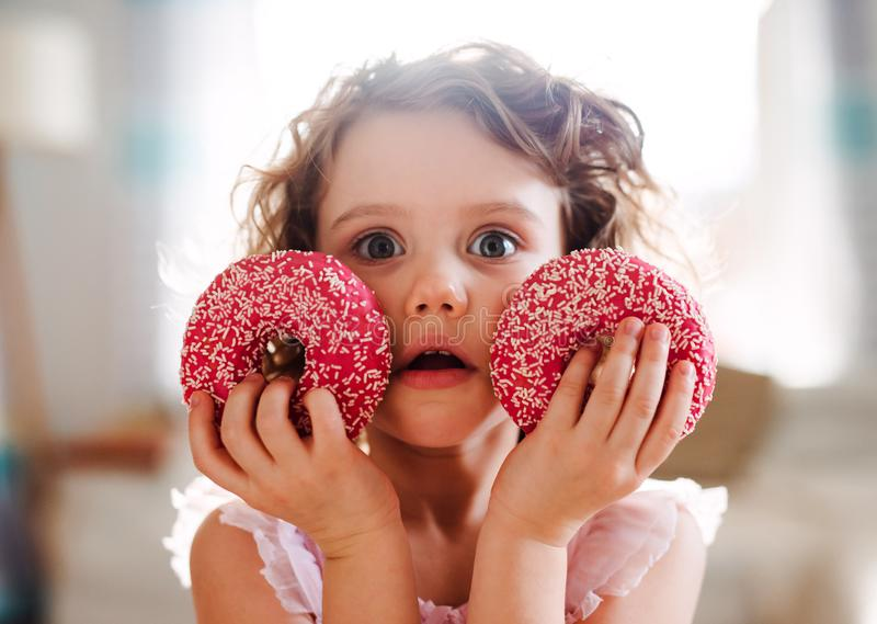 A small girl with doughnuts at home, looking at camera. A portrait of small girl with two doughnuts at home, looking at camera stock photography