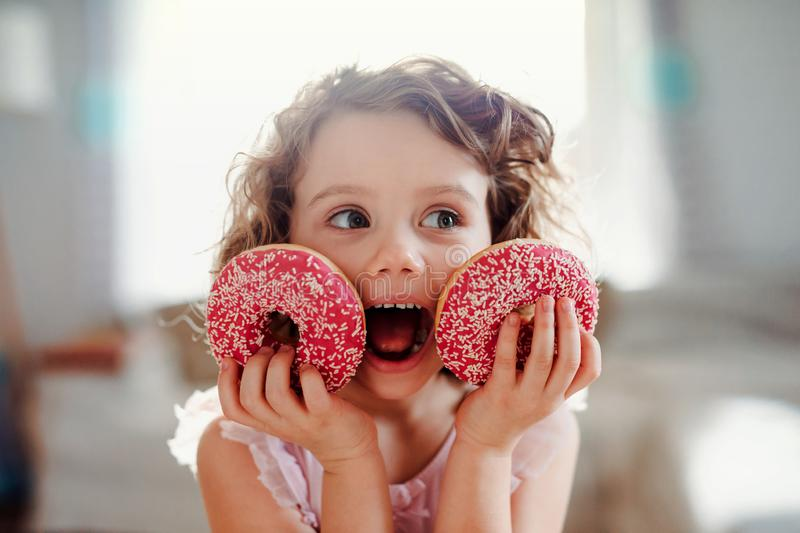 A small girl with doughnuts at home, looking at camera. A portrait of small girl with two doughnuts at home, looking at camera royalty free stock photo