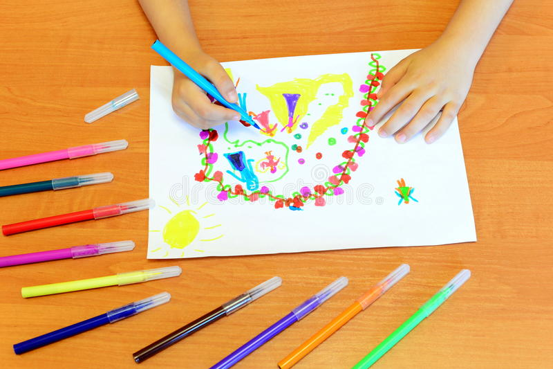 Small girl draws felt pens. Child holds a blue felt pen in hand and draws abstract princesses and flowers. A children drawing royalty free stock images