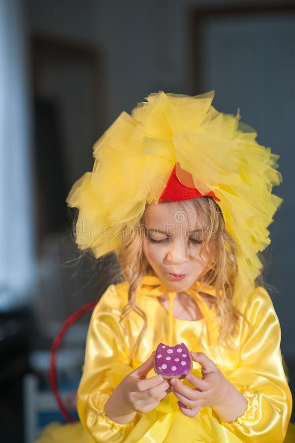 A small girl at Easter eats ginger cookies, painted eggs, laughs. Girl in the kitchen in a chicken suit.  royalty free stock photo